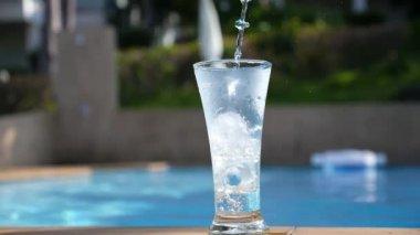 Flowing wody do szklanki z lodem w pobliżu basenu. Zwolnionym tempie. — Wideo stockowe
