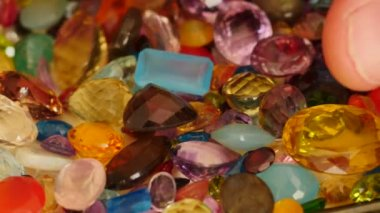 Man fingers move and turn some precious gemstones — Stock Video