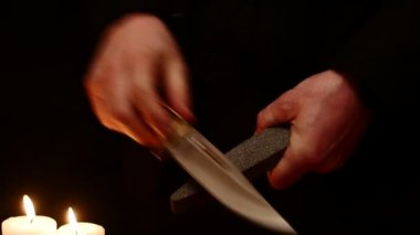 Isolated hands sharpening the battle knive — Stock Video