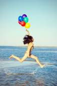Beautiful and athletic brunette girl with colorful balloons jump — Stock Photo