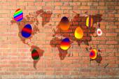 Colorful easter eggs on red brick wall texture with world map — Stock Photo