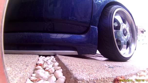 Conducir un coche bajado en un parque de coche de pendiente — Vídeo de stock