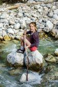 Teenage girl sitting on stone — Stockfoto