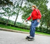 Red-haired teenage boy rollerskating — Stock Photo