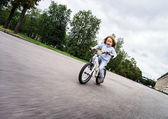 Cute little girl riding fast by bicycle — Stock Photo