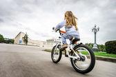 Roztomilá holčička na koni rychle na kole — Stock fotografie