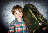 Emotional red-haired boy with suitcase — Stock Photo