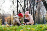 Two sisters playing in autumnal park — 图库照片