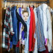 Cute little girl hiding inside wardrobe from her parents — Stock Photo #59795829