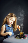 Cute little girl repair electronics by cooper-bit — Stock Photo