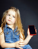 Cute little girl showing blank screen of modern smartphone — Stock Photo
