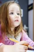 Cute little girl studing to speaking and writing letters at home — Stock Photo