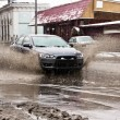 Dirty water splash from the car wheels at spring snowy street — Stock Photo #62140359