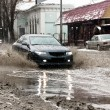 Dirty water splash from the car wheels at spring snowy street — Stock Photo #62140363