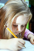 Cute little girl studing to speaking and writing letters at home — Stockfoto
