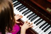 Little girl studing to play the piano — Stock fotografie