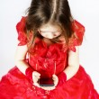 Cute little girl dressed in ball gown playing with smartphone — Stock Photo #63515363