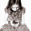 Cute little girl dressed in ball gown playing with smartphone — Stock Photo #63515369