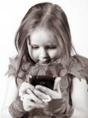 Cute little girl dressed in ball gown playing with smartphone  — ストック写真