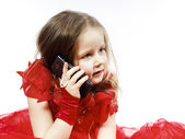 Cute little girl dressed in ball gown playing with smartphone  — Stock Photo