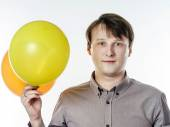 Young caucasian man holding yellow air balloons in his hand — Stock Photo