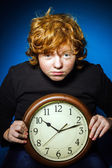 Expressive red-haired teenage boy showing time on big clock — Стоковое фото