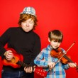 Two funny red-hair brothers playing music — Stock Photo #67189393