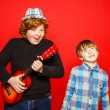 Two funny red-hair brothers playing music — Stock Photo #67189399