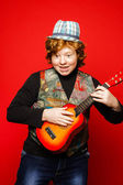 Red-hair funny teenage boy playing little guitar — Stock Photo