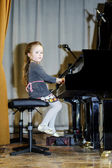 Cute little girl playing grand piano — Foto de Stock