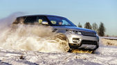Powerful 4x4 offroader car running on snow field — Stock Photo