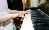 Girl's hands and piano keyboard close-up view — Stock Photo