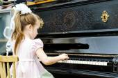 Cute little girl playing old piano — Stock Photo