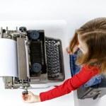 Cute little girl typing on vintage typewriter keyboard — Stock Photo #70980835