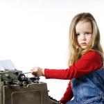 Cute little girl typing on vintage typewriter keyboard — Stock Photo #70980859