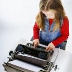 Cute little girl typing on vintage typewriter keyboard — Stock Photo #70980923