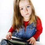 Cute little girl typing on vintage typewriter keyboard — Stock Photo #70981005