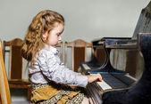 Bambina sveglia che gioca pianoforte nella scuola di musica — Foto Stock