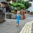 Cute little girl running along the street in a small village — Stock Photo #77974898
