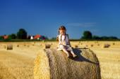 Funny cute little girl posing on the haystack in summer field — Stock Photo