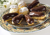 Eclair and cream puff cakes with flower — Stock Photo