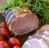 Crude, dried, organic gammon ham with tomotoes and juniper on plate — Stock Photo