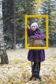 The girl in the frame and in the forest, catch the first snow in the palm of — Stock Photo