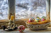 Basket with Easter eggs on the windowsill. — Stock Photo