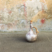 Old ceramic jug on a road near the oldness of the rough wall — Stock Photo