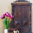Bright purple flowers tulips white vase, vintage old wardrobe an — Stock Photo #69464447