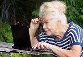 Senior woman looking at screen of laptop — Stock Photo