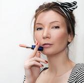 Portrait of girl smoking lipstick look at camera — Stock Photo