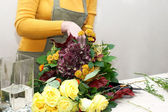 Florist making a bouquet of different cut flowers — Stock Photo