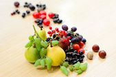 Berries, fruits, vegetables and nuts mixed on the table — Stock Photo